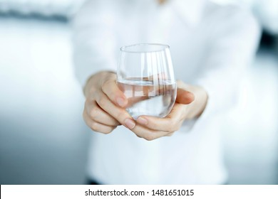 Cropped image of woman giving glass of water