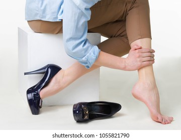 Cropped image of woman in high heels massaging her tired legs. Varicose veins concept. Painful varicose and spider veins on female legs. The young woman in heels massaging tired legs