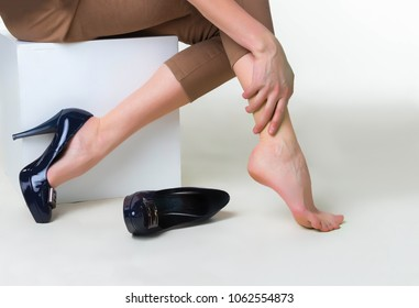 Cropped image of woman in high heels massaging her tired legs. Varicose veins concept. Painful varicose and spider veins on female legs. The young woman in heels massaging tired legs. Phlebology  DVT