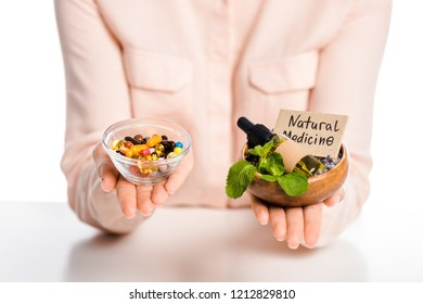 cropped image of woman holding bowls with natural medicine oil and pharmacological drugs isolated on white