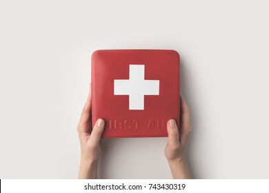 Cropped image of woman holding first-aid kit in hands