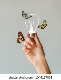Cropped image of woman holding a lamp with butterflies in her hand isolated on gray