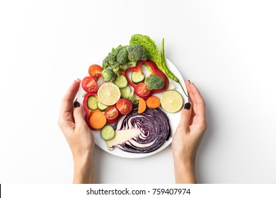Cropped image of woman holding plate with salad isolated on white