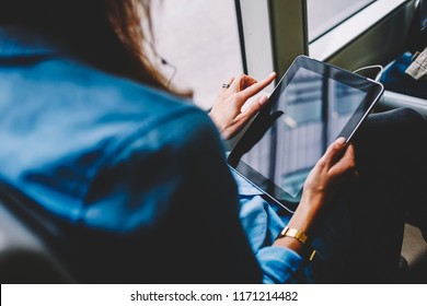 Cropped image of woman holding touchpad  reading book online via free wifi in bus, back view female using digital tablet for watching videos having good connection to internet in public transport