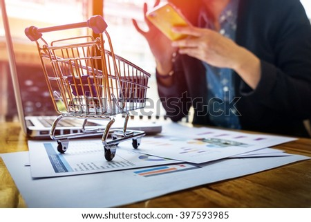 Cropped image of woman inputting card information and key on phone or laptop while shopping online.