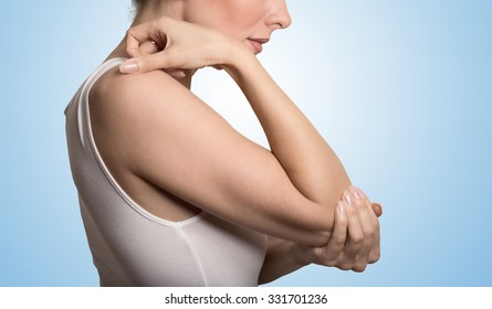 Cropped image woman with joint inflammation. Female's elbow. Arm pain and injury concept. Closeup side profile woman with painful elbow isolated on blue background
