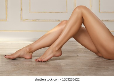 Cropped image of a woman lying on the floor with her long bare legs extending into the frame from the right