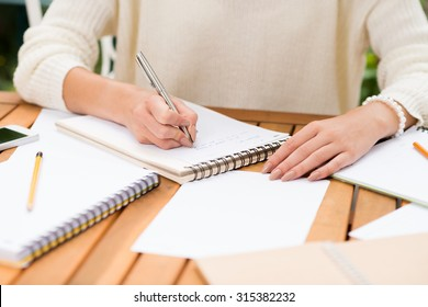 Cropped image of woman making notes in her notepad
