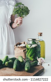 cropped image of woman preparing preserved organic cucumbers and holding dill at kitchen