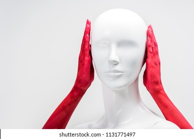 cropped image of woman in red paint covering mannequin ears isolated on white