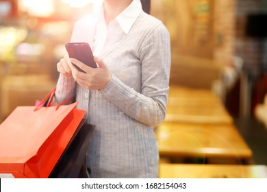 Cropped image of woman with shopping bags using mobile phone