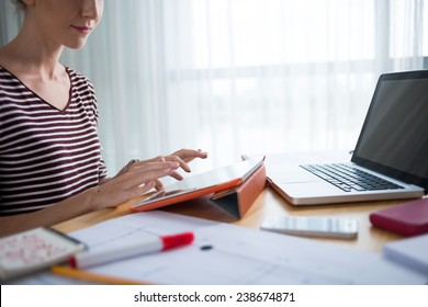 Cropped image of woman typing on digital tablet