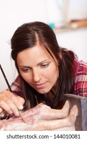 Cropped image of woman using brush on statue in workshop