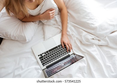 Cropped image of woman using laptop and lying on bed. Top view