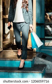 cropped image of woman walking from store with shopping bags and holding smartphone
