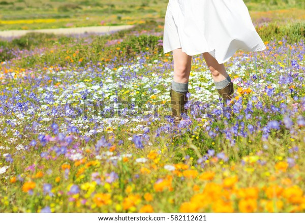 Cropped image of woman in a white dress walking in field of spring flowers
