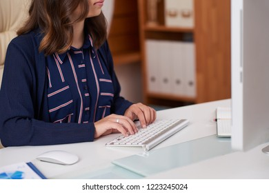 Cropped image of woman working on computer at ofice table