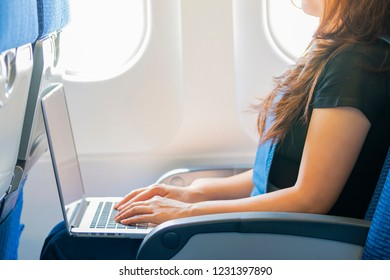 Cropped image of Woman working on her laptop computer on board of an airplane during the flight.