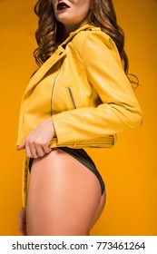 cropped image of woman in yellow leather jacket and black panties isolated on orange