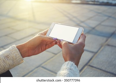 Cropped image of woman's hands holding cell telephone with blank copy space screen for your text message or advertising content, female watching video on smart phone while relaxing in the fresh air