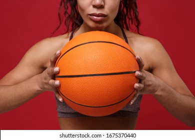 Cropped image of young african american sports fitness basketball player woman in sportswear working out isolated on red background in studio. Sport exercises healthy lifestyle concept. Holding ball