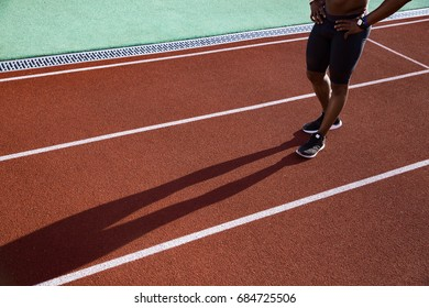 Cropped image of a young african sportsman resting after the race and walking with hands on hips at the stadium