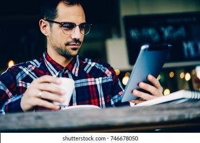 Cropped image of young bearded man in eyewear reading notification on modern tablet sitting in coffee shop.Smart student dressed in casual shirt installing new application on touch pad device