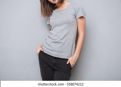Cropped image of a young casual woman in t-shirt standing isolated on a gray background