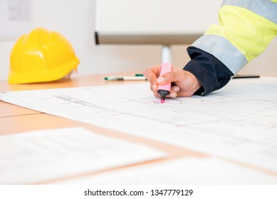 Cropped image of young contractor using pink highlighter on blueprint at office
