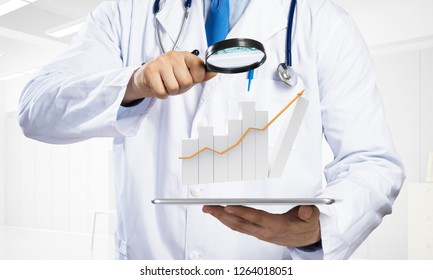 Cropped image of young doctor in sterile medical suit standing with tablet and graphical chart in his hands against bright office view on background.