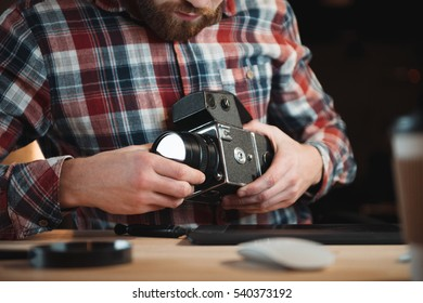 Cropped image of a young engineer fixing vintage camera while sitting at his workplace