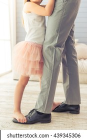 Cropped image of young father and his cute little daughter dancing at home. Girl is standing on her father's feet
