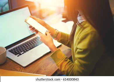 Cropped image of young female skilled blogger holding modern smartphone downloading multimedia files from laptop computer with mock up monitor connected to free wireless internet in coworking space