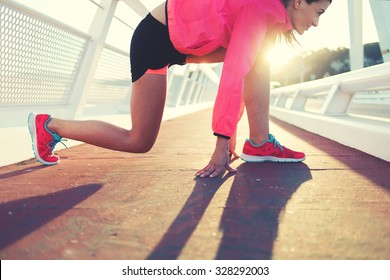 Cropped image of young fit woman in tracksuit took the position in preparation for her morning intense jog outdoors, sporty girl dressed in bright sportswear ready to start the run outside in evening