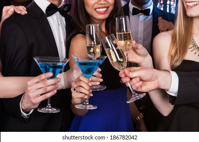 Cropped image of young friends toasting drinks at nightclub
