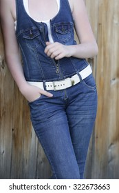 cropped image of a young girl in denim overalls on background of wooden gate