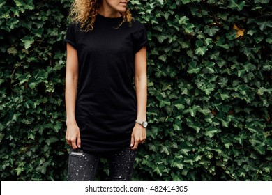 Cropped image of young hipster girl with curly hair wearing a blank black t-shirt and black jeans. mock-up of blank t-shirt. plants background. empty place for your text o design.