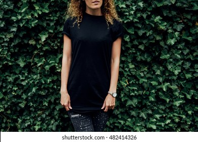 Cropped image of young hipster girl wearing blank black t-shirt and black jeans standing on a plants background, mock-up of blank t-shirt. empty place for your logo o design.