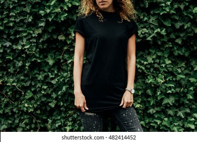 Cropped image of young hipster girl with curly hair wearing a blank black t-shirt and black jeans standing on a plants background, mock-up of blank t-shirt. empty place for your logo o design.