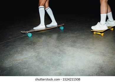 Cropped image of young hipster girls in streetwear riding skateboards at night outdoors