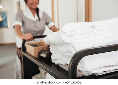 Cropped image of a young hotel maid bringing clean towels and other supplies