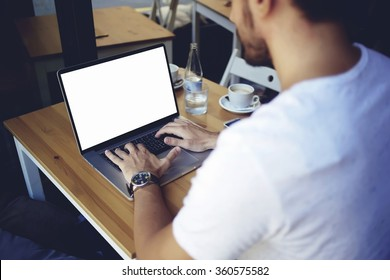 Cropped image of young man chatting via net-book during work break in coffee shop, male sitting in front open laptop computer with blank copy space screen for your text message or advertising content