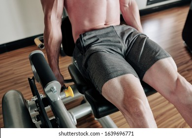 Cropped image of young man doing leg extension for quadriceps in gym machine
