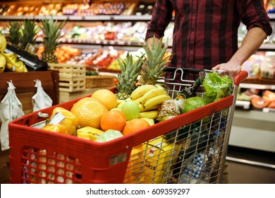 Cropped image of young man with shopping trolley choosing fruits in supermarket