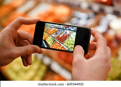 Cropped image of young man standing in supermarket make photo of products by phone.