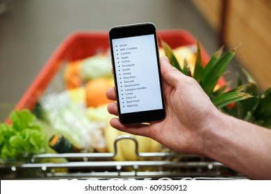 Cropped image of young man standing in supermarket looking at list of purchases in phone.