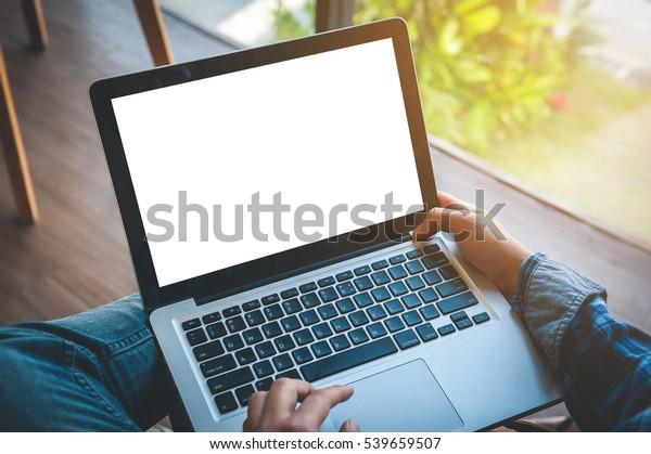 Bijgesneden beeld van een jonge man werken op zijn laptop in een coffeeshop, achteraanzicht van zakenman handen bezig met behulp van laptop op kantoor bureau, typen op computer zitten aan houten tafel