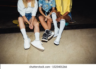 Cropped image of young multinational girls in streetwear sitting on skateboards at night party outdoors