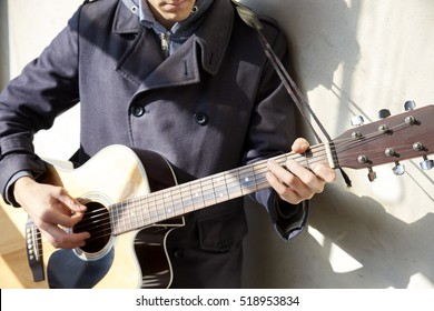 Cropped image of a young musician playing his acoustic guitar.
