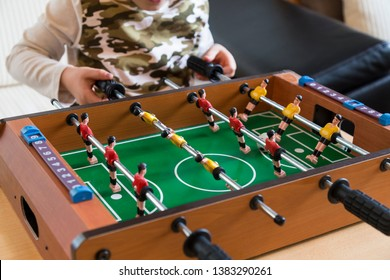 Cropped image of young people and children playing foosball while resting outdoors